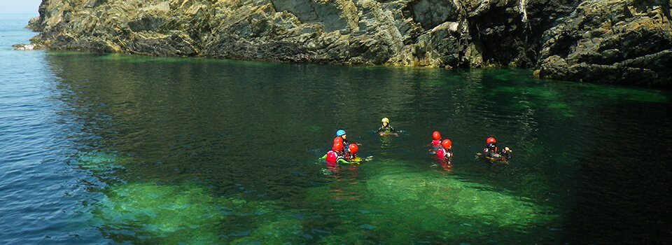 Family exploring the clear water, calm sea along north coast of Abereiddy Bay while Coasteering in Pembrokeshire Wales