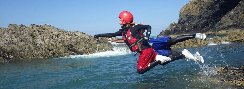 Children Superman dive while Coasteering in Pembrokeshire